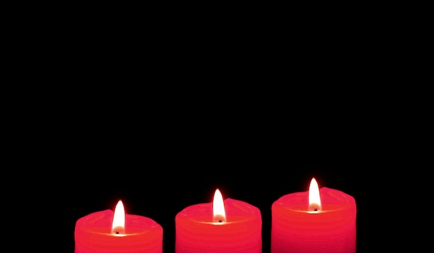Glowing red candles on the black background with free space