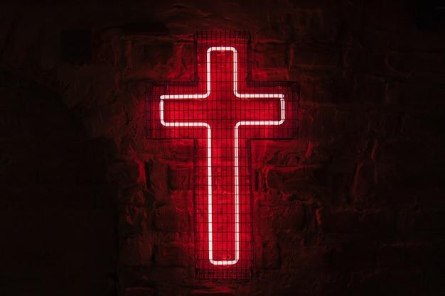 Светящийся красный неоновый крест висит на стене за решеткой в темноте.