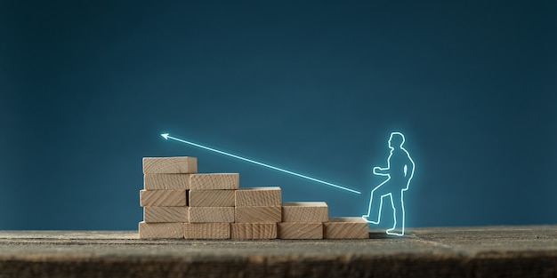 Glowing silhouette of a businessman on virtual interface following a glowing arrow upwards on wooden stairs in a conceptual image. over blue background.