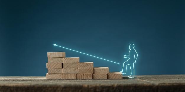 概念的なイメージで木製の階段の上向きに輝く矢印をたどる仮想インターフェイス上のビジネスマンの輝くシルエット。青い背景の上。