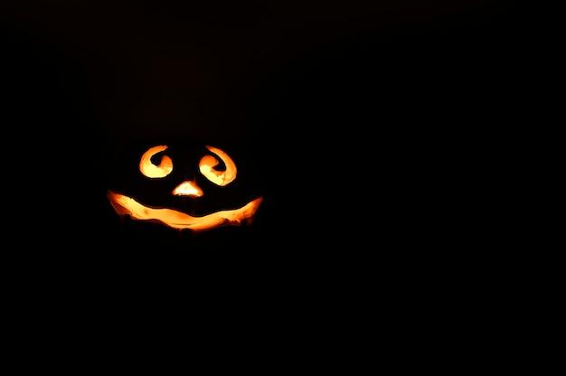 輝く笑顔ハロウィーンカボチャ、キャンドルホルダー、夜の暗い黒の背景で隔離。テキスト用のスペース