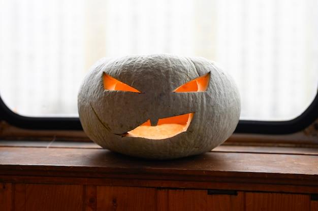 Светящаяся жуткая тыква на хэллоуин дома на столе
