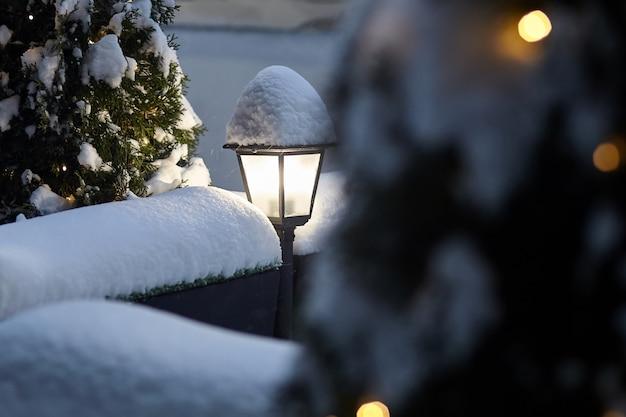 Светящийся уличный фонарь, покрытый снегом