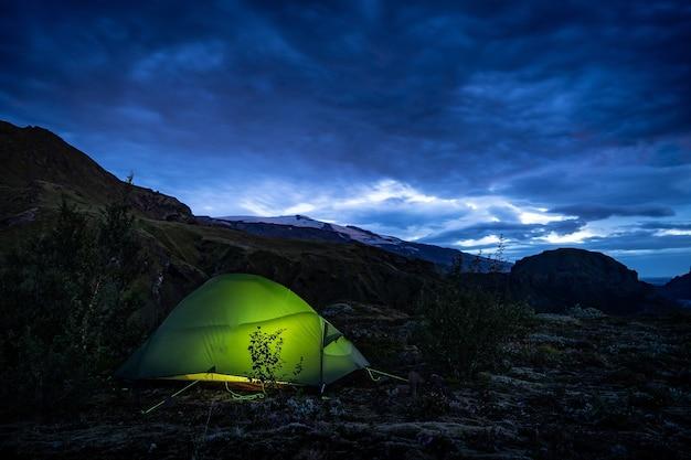Светящаяся палатка стоит в кемпинге ландманналаугар, исландия. сумерки, ночь. исландия.