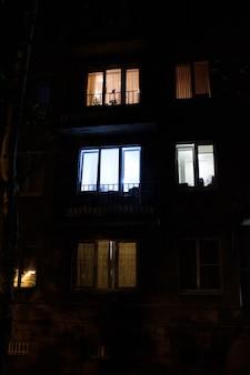 夜の住宅の高層ビルの輝く窓