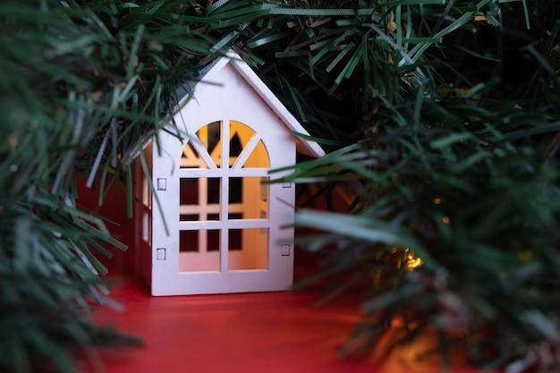木の上の輝く木製の居心地の良い家の花輪新年とクリスマスのコンセプト不動産のコンセプト