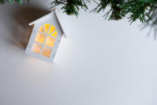 Светящийся деревянный дом гирлянда на елке на белом фоне.