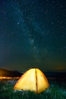 Glowing yellow tent in the mountains under a starry sky