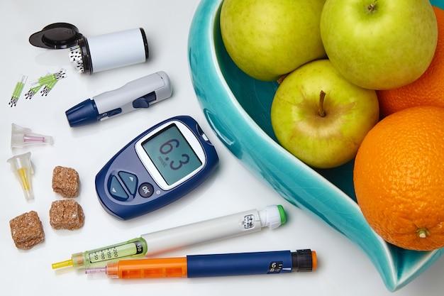 Глюкометр, инсулиновая шприц-ручка, сахарная ваза с яблоками и апельсинами на белом столе. концепция питания диабетиков
