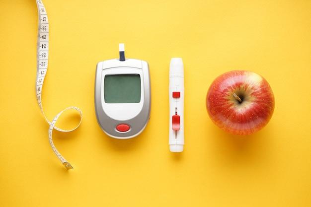 Глюкометр, ланцетная ручка, сантиметр и фрукты