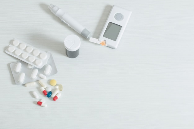 Glucometer and pills on  white wooden table