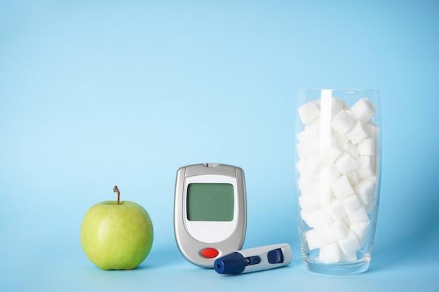 Глюкометр, сахар в стакане и яблоко
