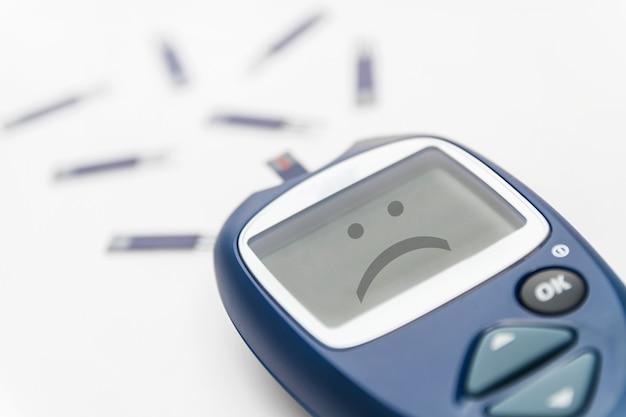 Глюкометр с тест-полоской с грустной улыбкой на мониторе