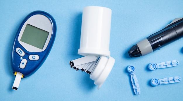 Глюкометр с тест-полосками и другими предметами. приборы для измерения глюкозы в крови
