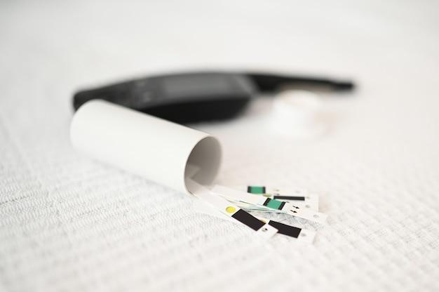 予備の針、glucometer、ストリップ、予備のストリップの箱、ペン型インジェクター付きのランセットの糖尿病セットのショットを閉じます。血糖値計血糖値計、糖尿病血糖値検査