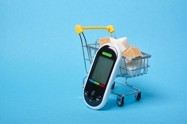 Глюкометр и коричневые и белые кубики сахара в тележке для покупок на синем пространстве для копирования
