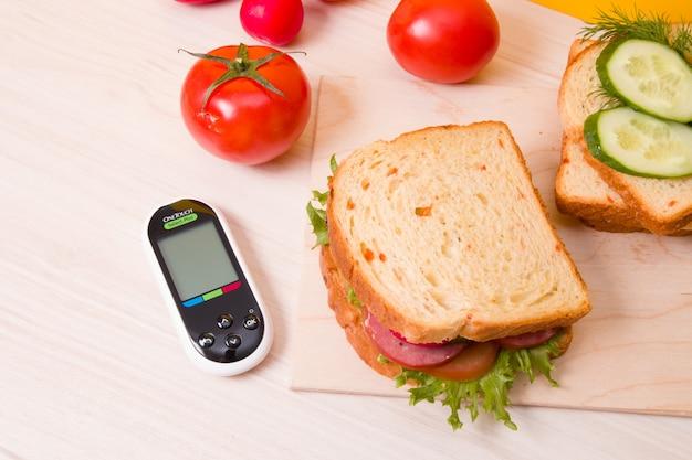 Измеритель глюкозы и здоровые бутерброды на деревянном столе