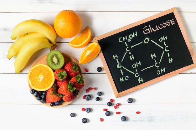 Glucose molecule on blackboard with mixed fresh fruits salad