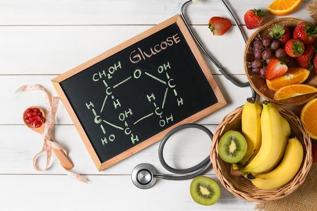 Glucose molecule on blackboard with mixed fresh fruits