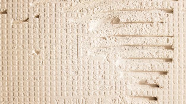 Клей для плитки с зубчатым рисунком. монтаж плитки. поверхность стены покрывается клеевым составом перед укладкой плитки или декоративного камня. ремонтные работы и концепция обновления.