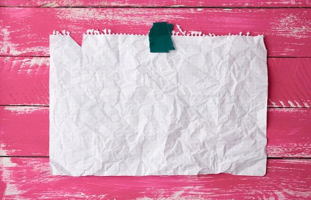 ピンクの木製の背景に紙の長方形の空の白いしわくちゃのシートを粘着テープで接着