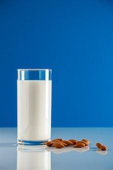 青い背景にグルテンフリーのアーモンドミルクスーパーフード健康的な食事のためのアーモンドミルクのガラス