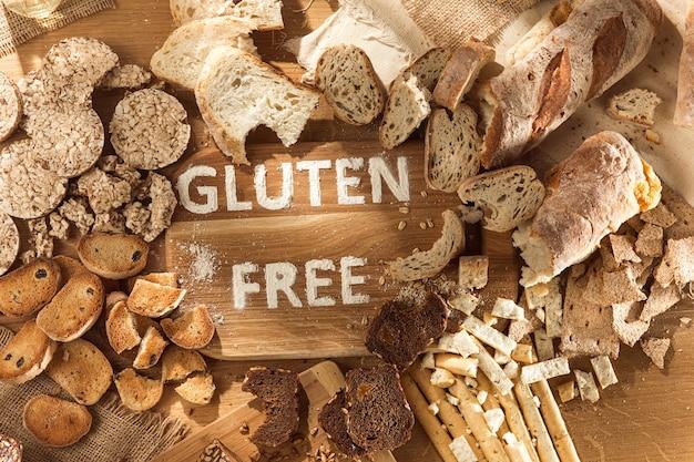 グルテンフリーの食品。トップビューから木製の背景にさまざまなパスタ、パン、スナック。健康とダイエットのコンセプトです。