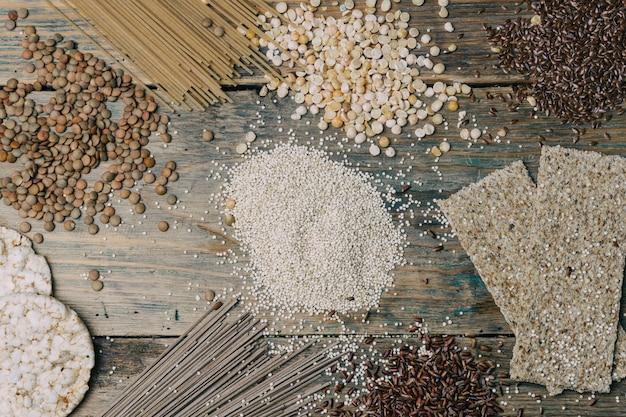 木製の背景にグルテンフリー穀物(玄米、エンドウ豆、亜麻の種子、レンズ豆、白いキノア)。