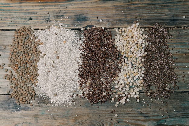 Gluten free grains ( brown rice, peas, flax seeds, lentils, white quinoa) on wooden background.