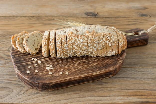 Веганский хлеб без глютена и без продуктов животного происхождения. вегетарианский хлеб с овсяными хлопьями со вкусом банана на деревянном деревенском столе, нарезанный и готовый к подаче.