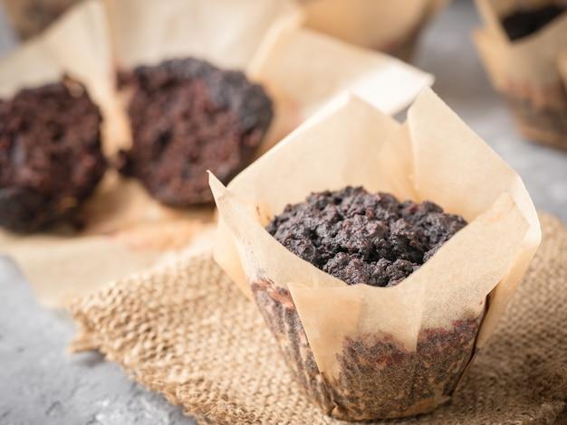 ビーツ、アーモンドパウダー、そば粉、カロブまたはココアを含むグルテンを含まないビーガンチョコレートマフィン。 copyspaceと灰色のコンクリート背景に自家製カップケーキ