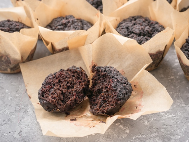 Gluten-free vegan chocolate muffins with beetroot, almond powder, buckwheat flour and karob or cocoa . homemade cupcakes on gray concrete background with copyspace