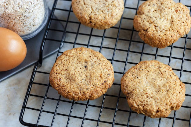 Glutenfree homemade oatmeal cookies, oats, egg on cooling rack. selective focus. toned photo.