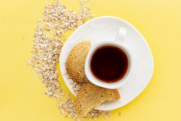 글루텐 프리 수제 귀리 오트밀 쿠키와 파스텔 옐로우에 차 또는 커피 에스프레소 잔