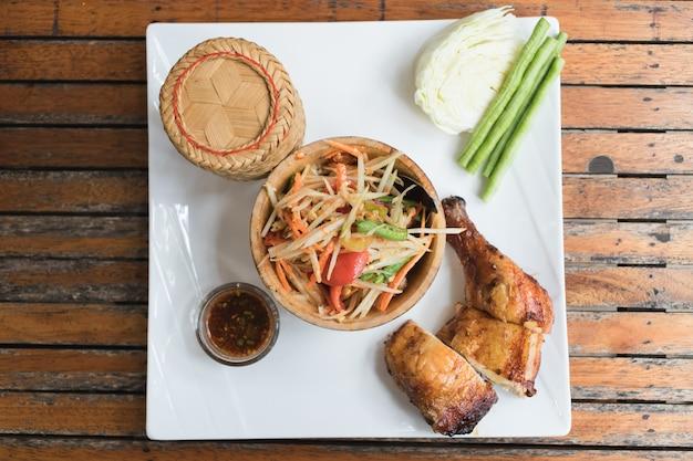 もち米、パパイヤサラダ、グリルチキンのディップソース、おかずとしての新鮮野菜が、木製のテーブルの上に置かれた美しい白いお皿に並べられています。
