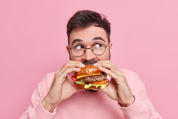 열성 및 과식 개념. 잘 생긴 수염 난 남자가 맛있는 햄버거를 물고 매우 배고픈 느낌이 들며 분홍색 벽에 둥근 안경 포즈를 취하고 치트 식사를 즐깁니다. 건강에 해로운 식사