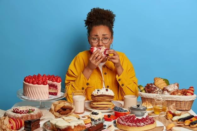 열성 및 과식 개념. 화가 우는 민족 여자는 마지 못해 케이크 조각을 먹고, 파란색 벽 위에 고립 된 많은 디저트와 함께 테이블에 앉아