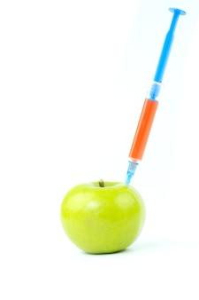白い背景の上の注射器とgmoリンゴ
