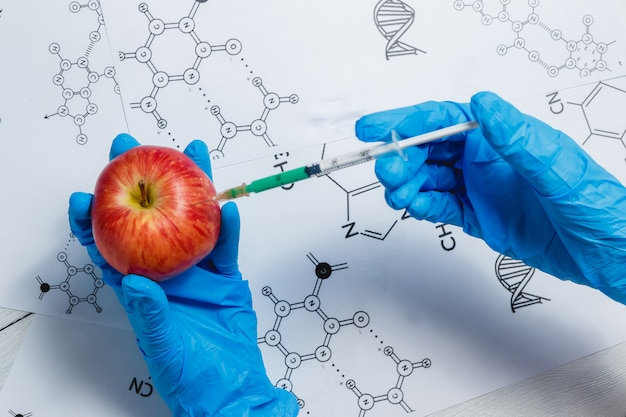 Gmo scientist injecting green liquid from syringe into apple - genetically modified food concept.