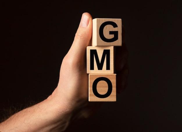 Слово gmo на кубических блоках в мужской руке на черном фоне с копией пространства