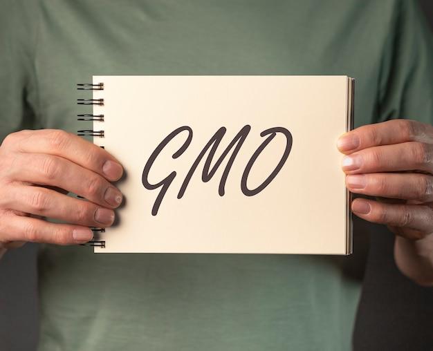 Гмо слово на бумажном блокноте в мужской руке