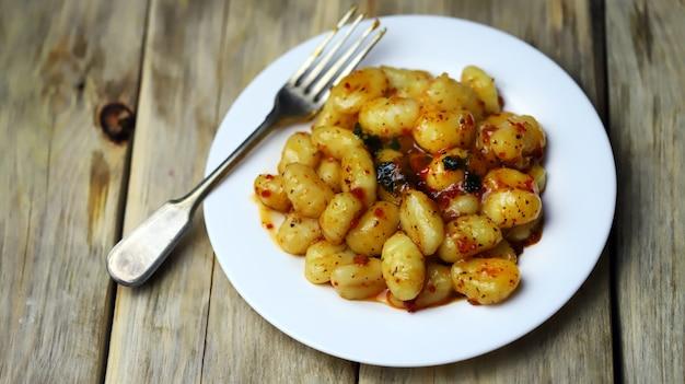Gnocchi in chili tomato sauce on a white plate.