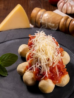 Gnocchi with natural organic tomato sauce without pesticides with grated parmesan cheese and basil leaves..