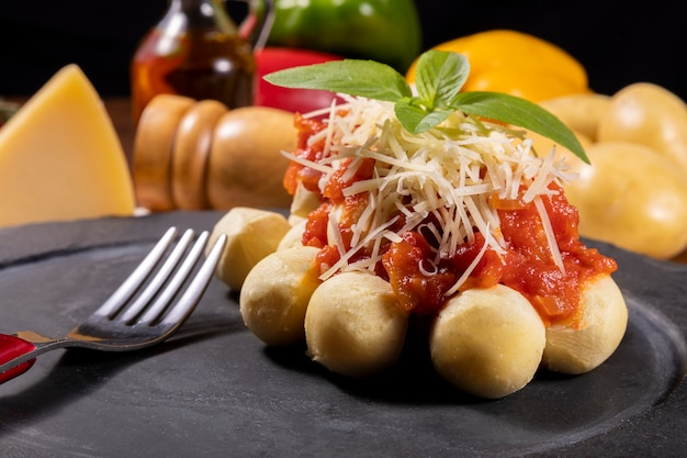 Gnocchi with natural organic tomato sauce without pesticides with grated parmesan cheese and basil leaves.