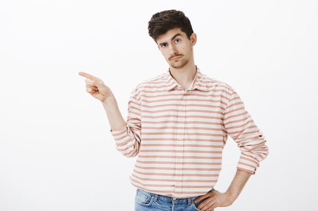 Go away from here, i demand. intrigued handsome male model with moustache, pointing left with index finger and lifting eyebrow, being curious and confident over gray wall