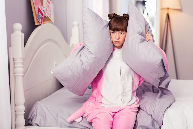 Go away. pretty teenager wearing pajama while sitting on her bed