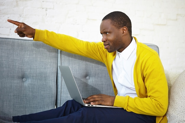 Go away. sideways shot of attractive young dark skinned man having angry look, being disturbed by someone while watching movie online on laptop, sitting on couch and pointing finger at door