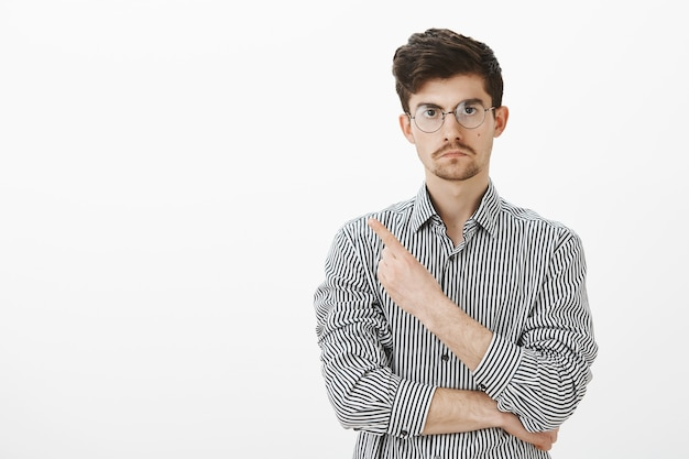 Go away, do not want see you. angry fed up european male coworker in glasses and striped shirt, pointing back or at upper left corner, being displeased and angry, asking to leave over gray wall