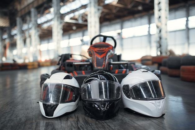 Картинговая машина и шлемы на земле, картинг авто спорт в помещении. скоростной картинг. соревнование на быстрых транспортных средствах, по горячим следам