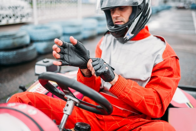 Go-kart driver in helmet on karting speed track. carting race